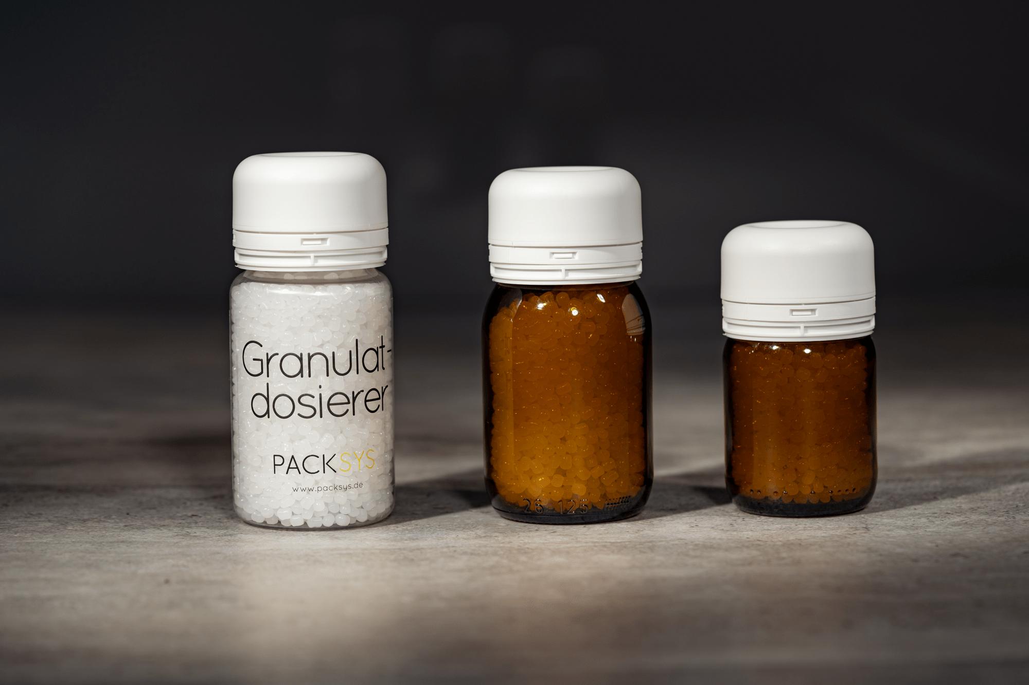 Drei Größen Granulatdosierer in einer Reihe: Kunststoff- und Glasbehälter
